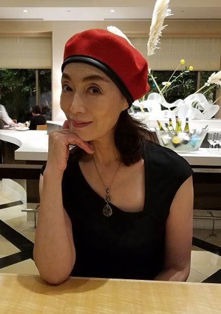 赤い帽子を被って机に肘をついて座る島田陽子