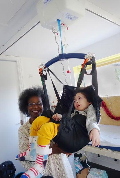週3回2~3時間、自宅訪問してくれる介護スタッフが、息子をリフトに乗せ車いすへと運ぶ(撮影/ユミコ・リトル)