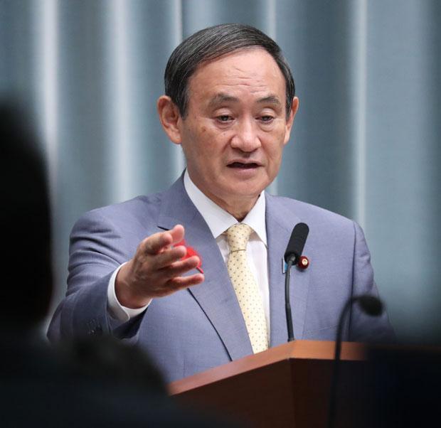 臨時閣議で消費税率引き上げを決めた10月15日、記者会見したのは安倍首相ではなく菅官房長官だった (c)朝日新聞社