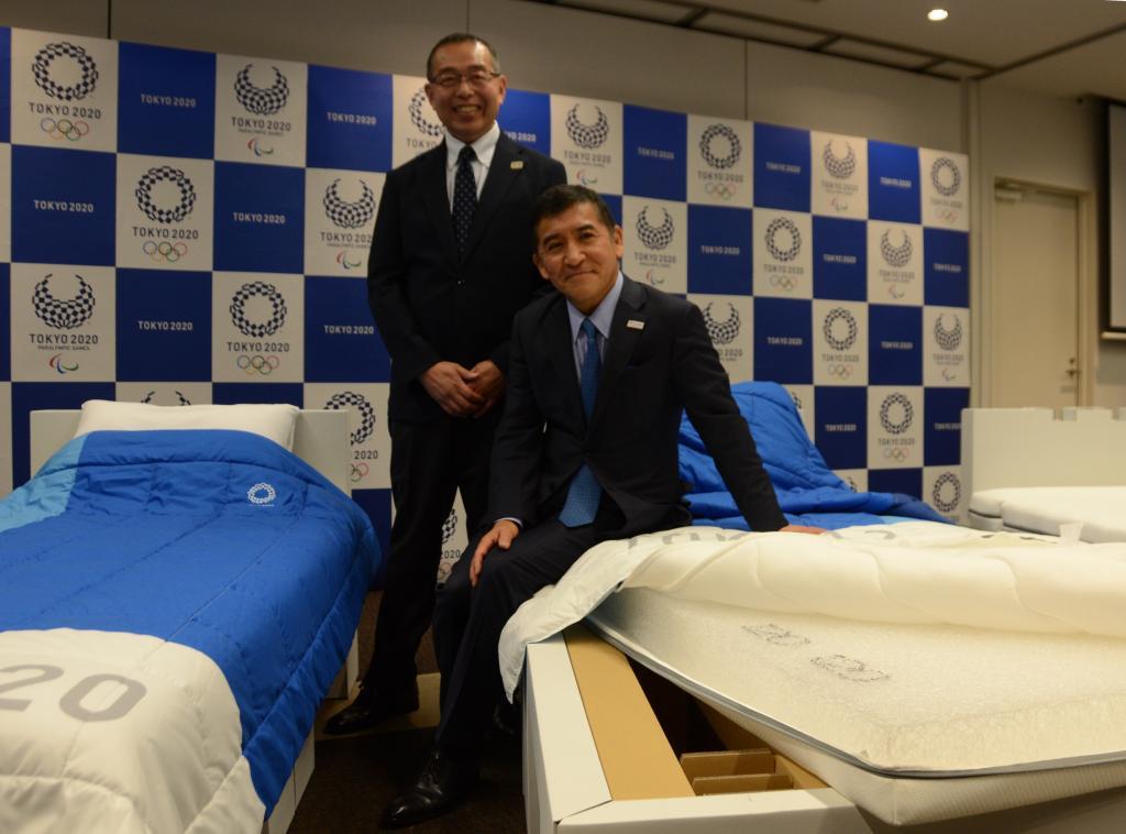 選手村に導入された段ボールベット寝具。大会組織委員会の北島隆・ビレッジゼネラルマネージャー(左)とエアウィーヴの高岡本州会長(C)朝日新聞社